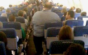 Zwaarlijvige persoon die niet tussen de armsteunen van een vliegtuigzetel past.