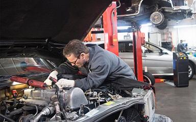 Automechanieker aan het werk in de motorkap